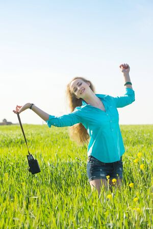 young blond hair woman with vintage medium format photo camera in a green wheat field