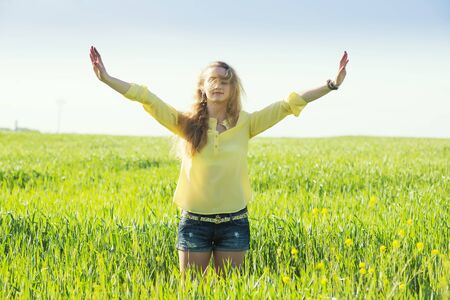 young blond hair woman poses in a summer green wheat field. young woman enjoy of freedom feel