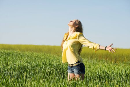 portrait of young blond hair woman who feels inspiration and freedom in summer green wheat field