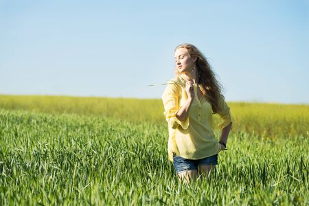 young blond woman poses in a summer green wheat field. young woman enjoy  of freedom feel Stok Fotoğraf
