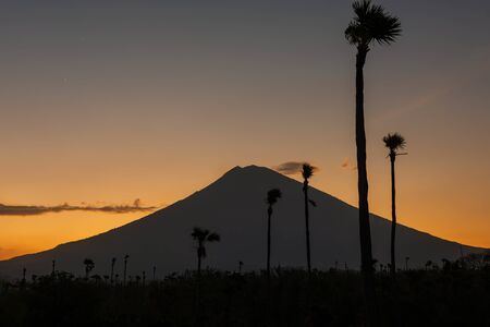 Orange sunset above Agung volcano, Bali island. silhouette of Volcano, view from black sand beach at dusk, Indonesia.