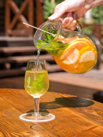 female hand holding and pouring from jug white summer wine sangria with fruits to a glass on summer restaurant terrace