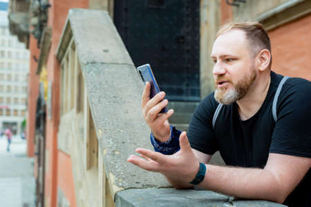 adult man has a video call on smartphone, he speaks by smartphone outdoor in a city