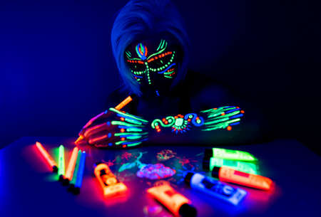 Portrait of woman with neon makeup, which made of fluorescent paint in ultraviolet light.