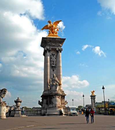 People walking near gilded Fames sculptures on the socle counterweights of Pont Alexandre III over the river Seine in Paris, France