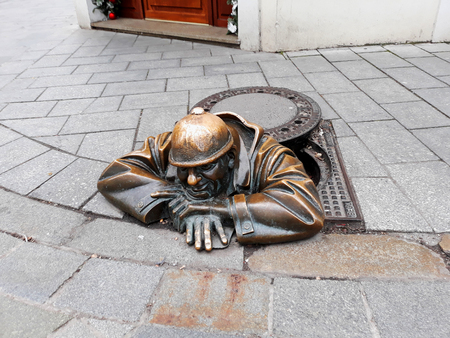 Bratislava, Slovakia - 15 December 2017: Bronze sculpture of a man watching passersby from a manhole. It is called Cumil or the Watcher and has become a symbol of the old town Editorial