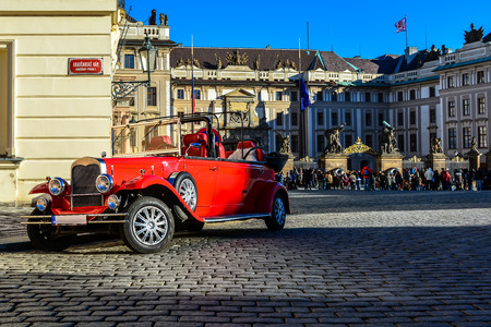 Vintage red car with the Prague Castle in the background. These are historical Praga-brand Czech vehicles, manufactured in the period from 1928 to 1935. 에디토리얼