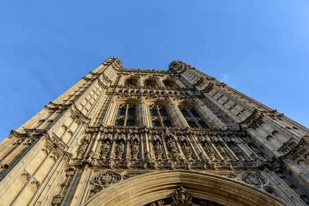 A view of the neo-Gothic Victoria Tower of the Palace of Westminster from low angle against the blue sky