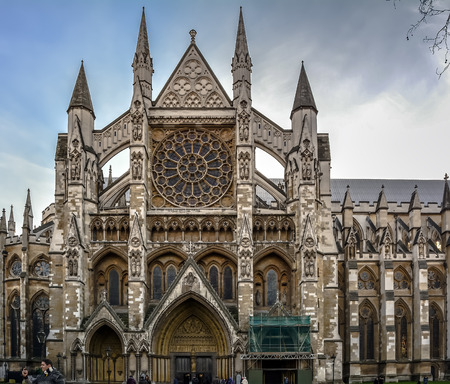 Exterior view of the North Trancsept of Westminster Abbey, entrance with three doorways. Gothic arches, large rose window, flying buttresses and pinnacles.