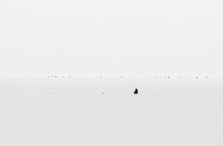 Winter fishing on iced lake, natural background. Minimalist style scenic aerial view. Black and white tones in minimalist photography.