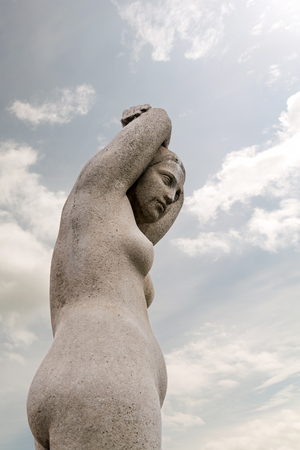 Barcelona, Spain - May 8, 2018: Statue of naked female with her arms over her head against the blue sky.