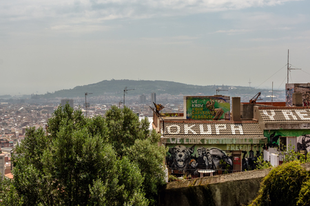 Barcelona, Spain - May 9, 2018: View to the squatted social center roof from Park Guell. Roof sign