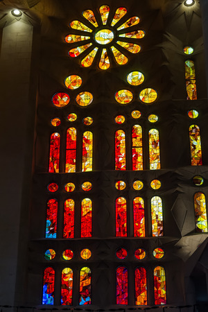 Orange geometric stained glass designs in Sagrada Familia window, Barcelona, Spain. Each unit is named after a person or place of religious significance and relevance to the basilica.