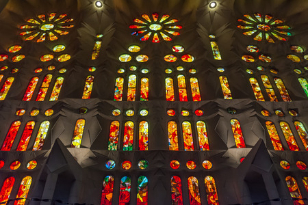 Orange geometric stained glass designs in Sagrada Familia windows, Barcelona, Spain. Each unit is named after a person or place of religious significance and relevance to the basilica.