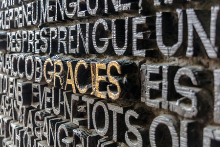 Detail with word Gracies (Thanks in catalan) on the bronze door of Passion facade of Sagrada Familia in Barcelona. The gospel doors contain text from the New Testament depicting the Passion of Christ.