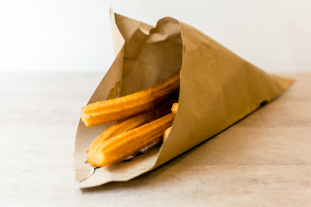Traditional Spanish dessert churros in brown paper cone. A churro is a fried-dough pastry based snack. Its surface is ridged due to having been piped from a churrera - a tool with star-shaped nozzle.