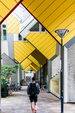Rotterdam, Netherlands - May 22, 2018: Man walking through repeating cube pattern of Cube Houses. It is a set of innovative houses based on the concept of high density housing with sufficient space.