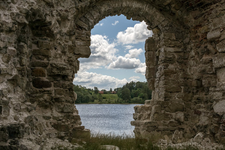 River and clouds through ruins of Koknese Castle - one of the largest medieval castles in Latvia. Construction of hydroelectric dam in 1965 partially submerged the castle and surrounding valley.