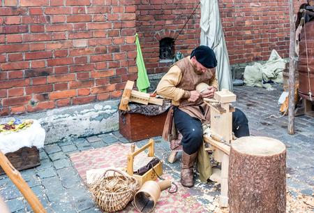 Riga, Latvia - August 18, 2018: Woodcarver working at medieval crafts market during Riga City Festival. Standard-Bild - 120378333