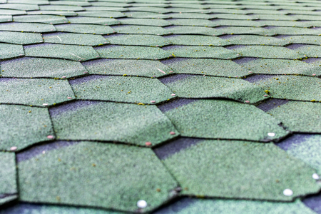 Fragment of green shingle tile texture roof for background. Closeup detail. Flexible soft built-up bituminous roofing.