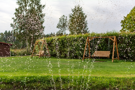 Two wooden swing benches in the garden with water drops in the foreground. Fountain water drops in the air with wooden garden swings in the background. Country summer view. Фото со стока