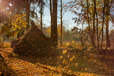 Old reed dwelling of the ancient tribe of Latgallians sprinkled with orange autumn leaves in a reconstructed Stone Age settlement of Archaeological Site in Gauja National Park, Araisi, Latvia.