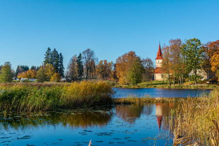 Araisi Lutheran Church standing on the calm lake shore in sunny autumn day. Ancient church reflecting in the calm blue smooth surface of the lake.