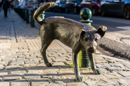 Brussels, Belgium - December 13, 2018: Het Zinneke, sometimes wrongly called Zinneke Pis - a bronze statue of peeing dog lifting his leg onto a Brussels street pole.
