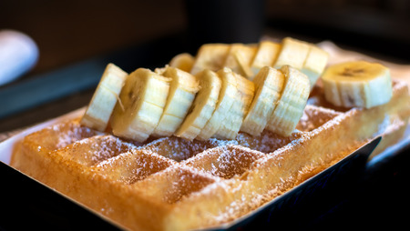 Fresh square Belgian waffle with cut banana topping and sugar powder for breakfast on dark background. Imagens