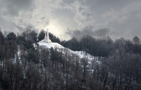 View to the white Three Crosses - a prominent monument in Vilnius, Lithuania, on the Hill of Three Crosses, originally known as the Bald Hill, under dramatic cloudy winter sky.