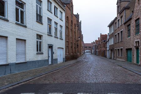 Picturesque old street of Bruges with traditional medieval houses and cobbled road in slight morning fog. Cityscape of Bruges streets.