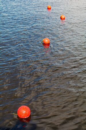 Four bright orange buoys floating on river water surface. Set of four orange safety buoys stretching into the distance in a river with small waves on water surface.