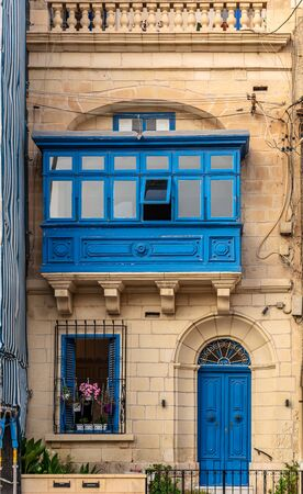 Residential house facade with blue door, window shutters and traditional Maltese wooden enclosed balcony in Sliema, Malta. Authentic Maltese urban scene.