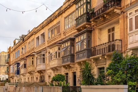 Residential house facade with traditional Maltese wooden balconies in Sliema, Malta, coloured in orange with evening sunlight. Authentic Maltese urban scene.