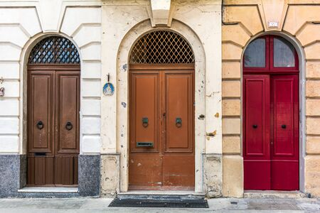 Three old wooden arched doors, brown and red, decorated with iron door knockers and molding. Vintage entry doors in Valletta, Malta.