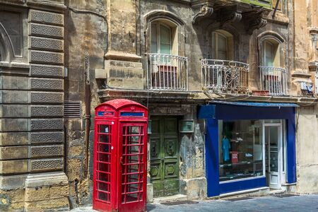 London-style iconic red phone box standing next to run-down old building and bright show-window of clothing store in Valletta, Malta. Stock fotó