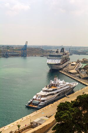 Luxury white yacht and passenger ship in Cruise Port of Valletta shot from Lower Barrakka Gardens in summer day. Stock fotó