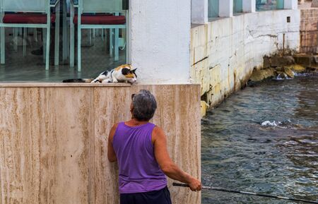 Valletta, Malta - August 30, 2019: Maltese fisherman patting stray calico cat while catching the fish with rod in another hand. Friendship of man and cat. Man caring for street cats. Editorial