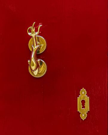 Fragment of red wooden door with golden vintage knocker as dolphin with a trident-shaped tails and golden decorative key-hole. Crimson red door with golden hardware.