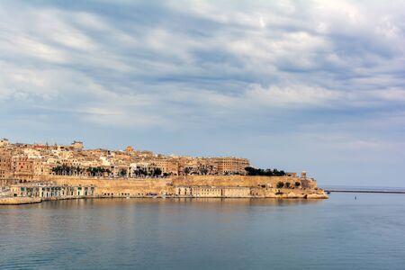 Magnificent view of Valletta from Senglea Gardjola gardens. Valletta reflecting in calm Mediterranean sea under clouds.