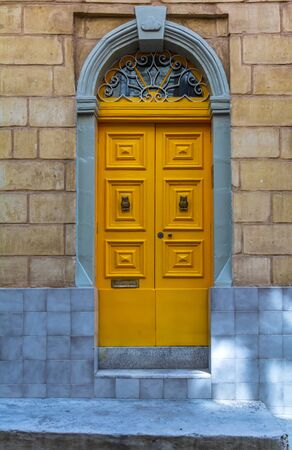 Historical ornate wooden yellow door in a stone entry in Bormla, Malta. With glass window above. Architectural theme.
