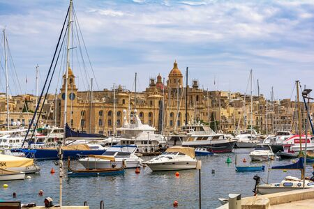 Cospicua, Malta - September 1, 2019: Yachts and boats anchored at Grand Harbour Marina of Birgu (Vittoriosa) in Malta, with Malta Maritime Museum building.