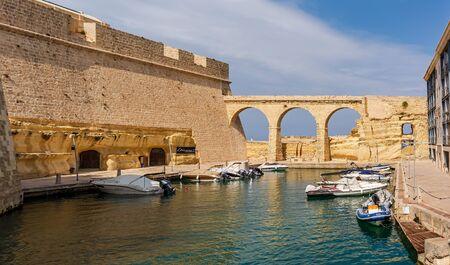Birgu, Malta - September 1, 2019: The ditch turned into moat that separates Fort St Angelo from Birgu. Redakční