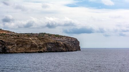 Steep cliff leading to Mediterranean Sea in the South of Malta. Stock Photo