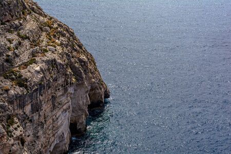 Steep cliff leading to Mediterranean Sea in the South of Malta. Stock Photo - 135130290