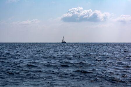 Sailboat in the Mediterranean sea ay horizon. Mediterranean sea scene.