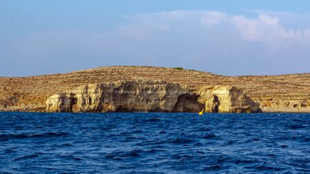 Rocky edges of the Comino island sticking out from Mediterranean Sea and lit by the orange evening sun. Rock formations with caves.