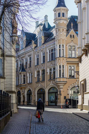 Riga, Latvia - April 5, 2020: Lonely homeless man strolling at empty street of Old Riga Town with eclectic Gothic building. City center in coronavirus COVID-19 pandemic quarantine time.