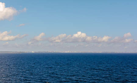White cumulus clouds in sky over blue  water of Gulf of Finland landscape, with vague silhouette of Finland in the horizon. Big cloud above sea.