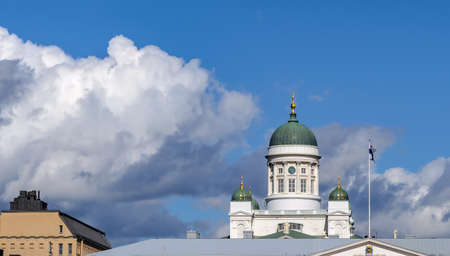 Main neoclassical green dome of white Helsinki Cathedral with a clock, surrounded by smaller domes against cloudy blue sky.